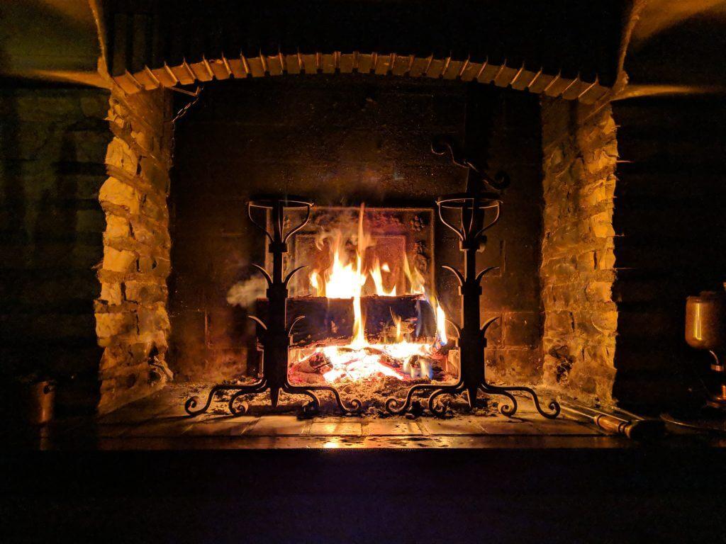Roaring fireplace in cozy setting.