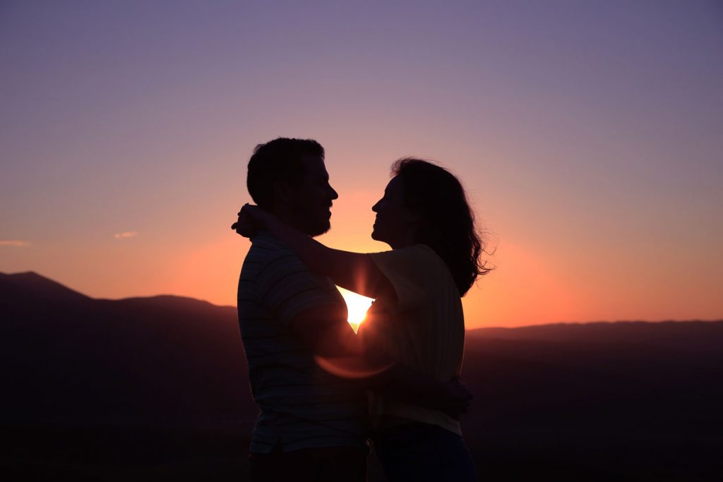 A couple embracing in the sunset.
