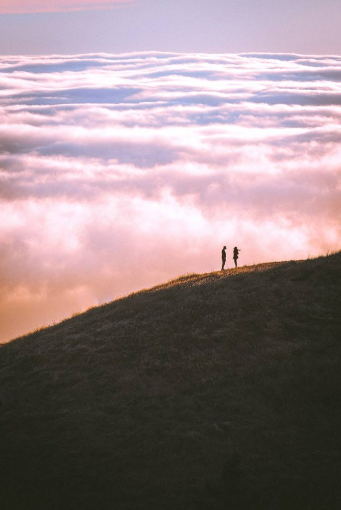 Couple faraway posing on a hillside at sunset.