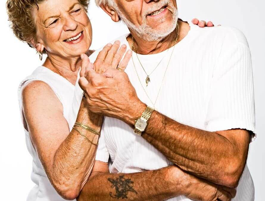 Older couple in white tees smiling and dancing.
