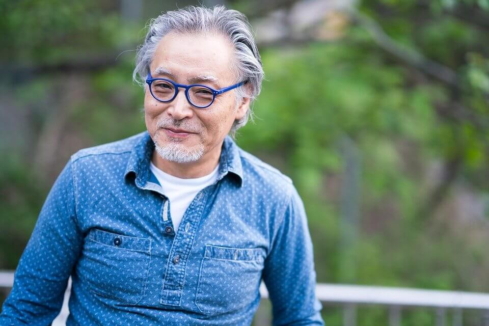 Man in blue shirt and blue glasses smiling