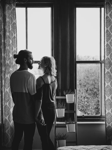 Man and woman facing each other by window.