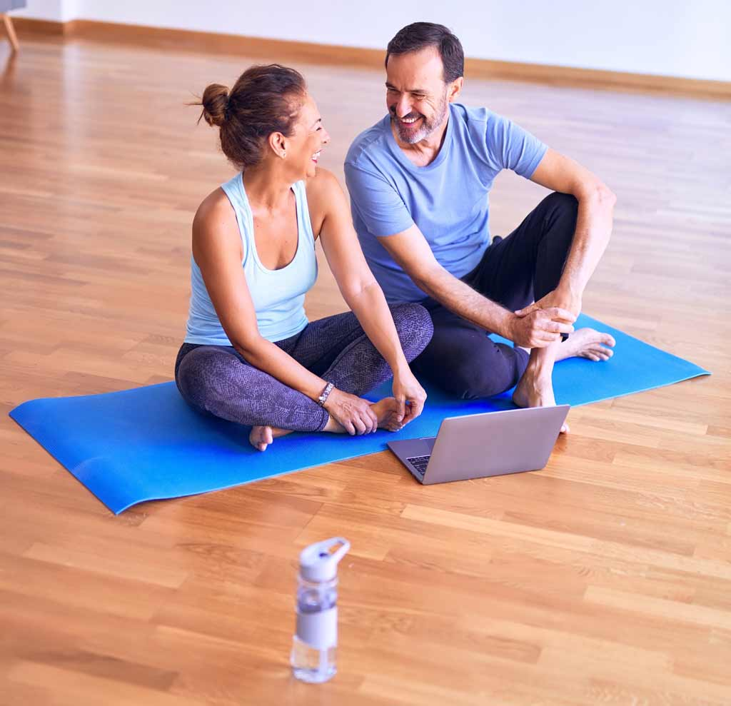Man and woman sitting on a yoga mat smiling.