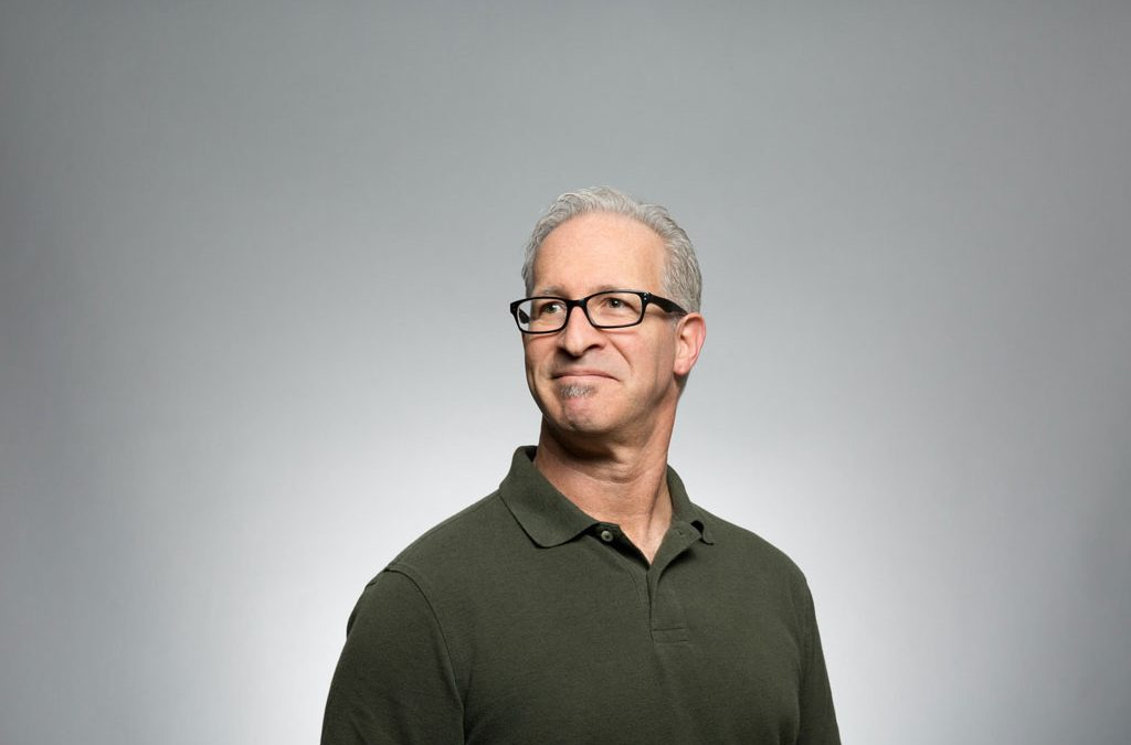 Middle aged man in green polo with grey hair and glasses.