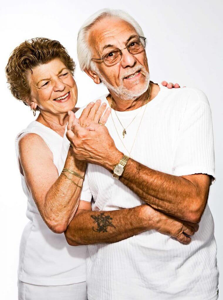 Older couple happily embracing in white outfits.