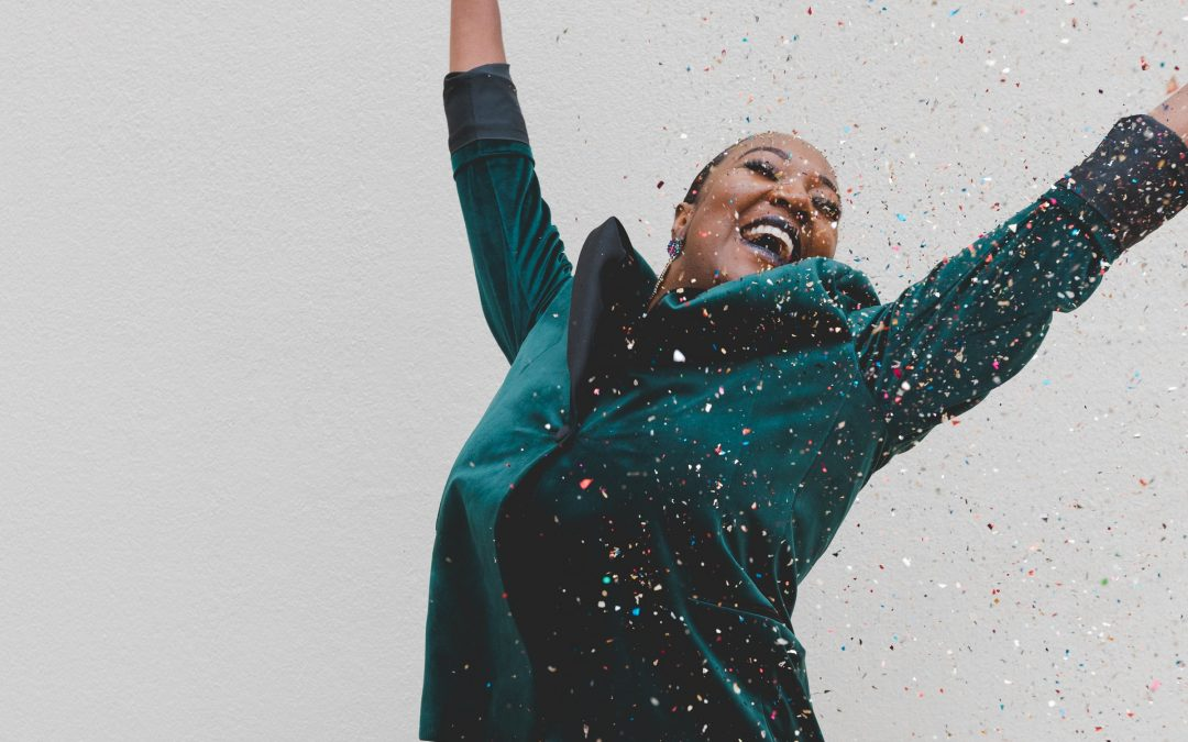 Woman jumping up in confetti.