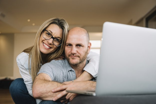 Couple showing love and affection with laptop in front