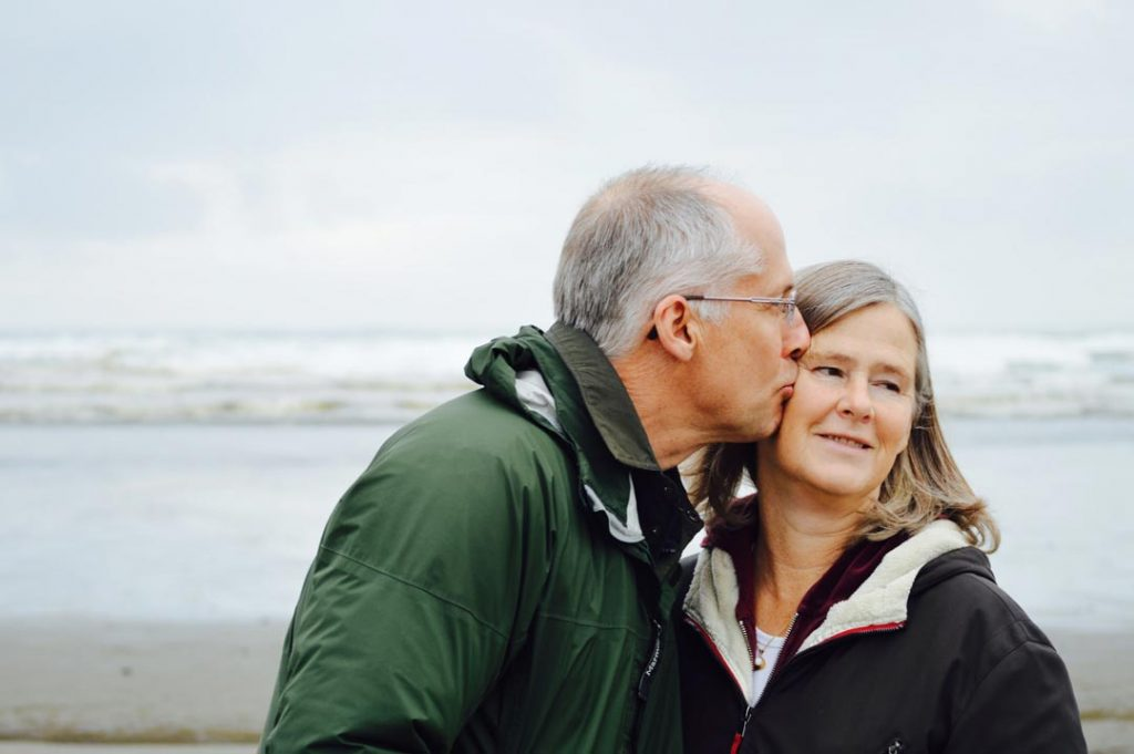 A husband kissing his wife on the beach